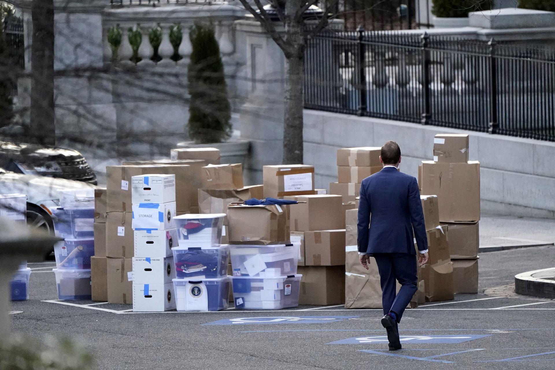 2021年1月14日,一名男子从白宫大楼西翼外的艾森豪威尔行政办公楼搬出来的大堆箱子旁走过。(AP)