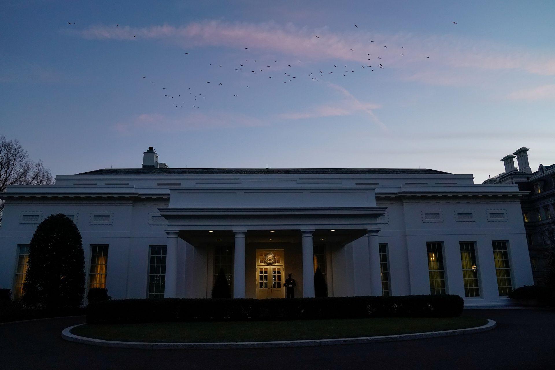 2021年1月14日,日落时分,美国华盛顿白宫上空有小鸟飞过白宫西翼。(Reuters)